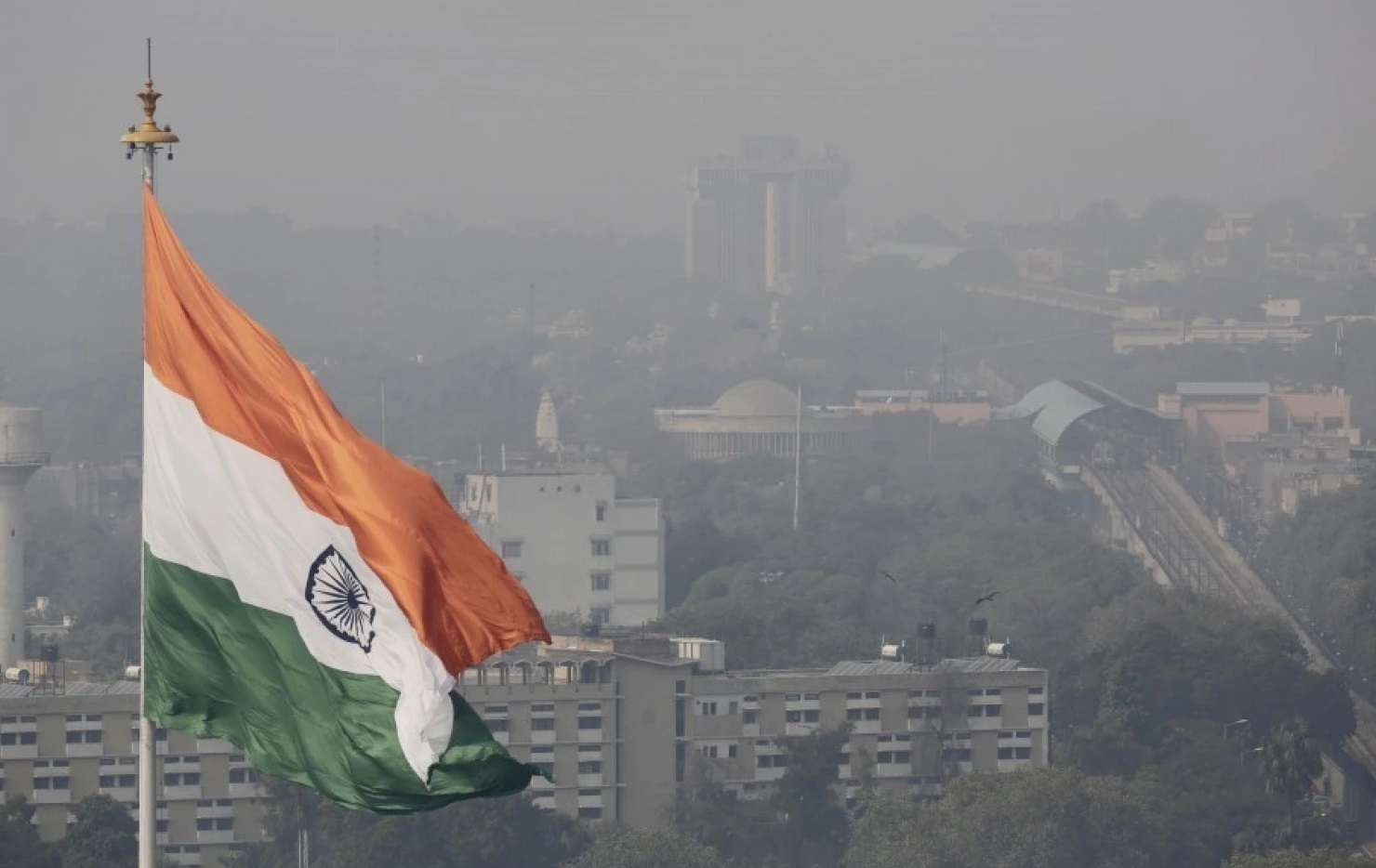 An Indian national flag flies as a thick layer of smog envelops the city skyline after Diwali festival, in New Delhi, India. New Delhi is imposing new rules to reduce its notoriously snarled traffic and fight extreme air pollution that has earned India's capital the title of world's most polluted city.