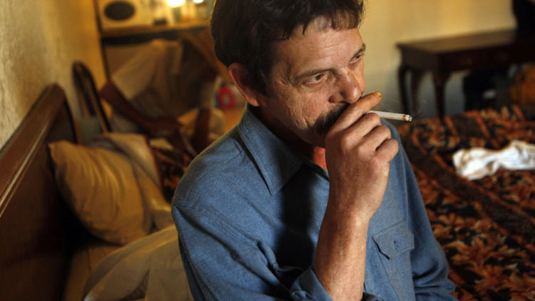 Steve Schulman, 56, smokes a cigarette in his hotel room at the Palm Tree Inn in North Hills in November of 2009.