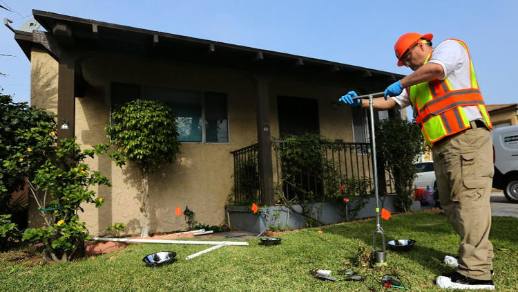 An L.A. County environmental health specialist collects a soil sample in Commerce.