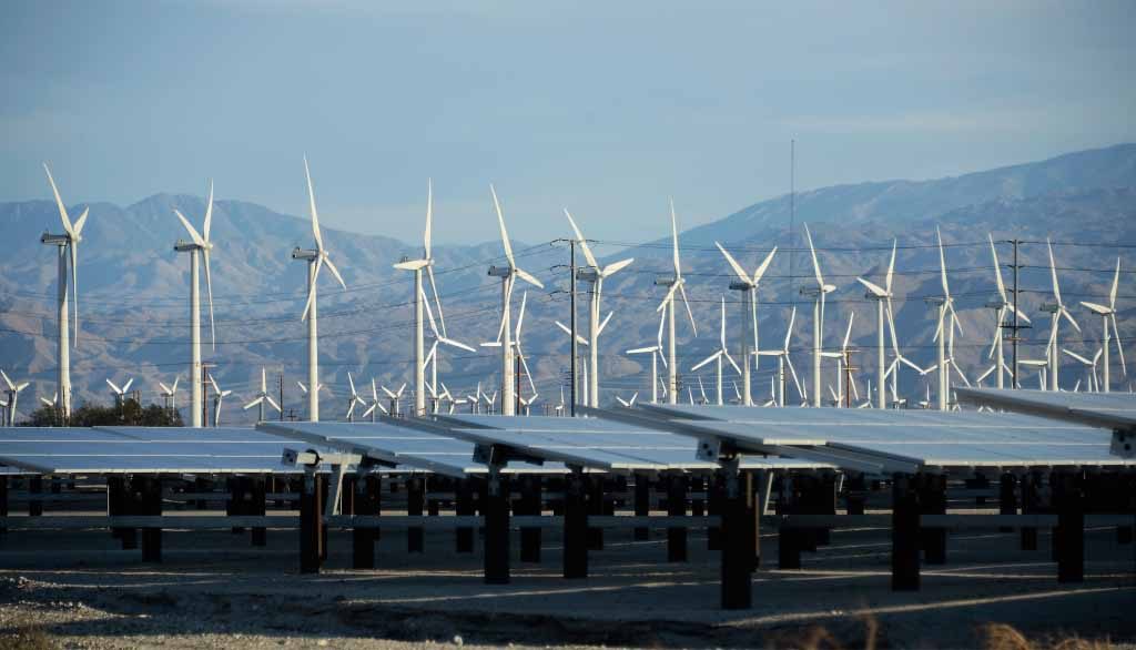 Giant wind turbines are powered by strong winds in front of solar panels on March 27, 2013 in Palm Springs, California. According to reports, California continues to lead the nation in green technology and has the lowest greenhouse gas emissions per capita, even with a growing economy and population.
